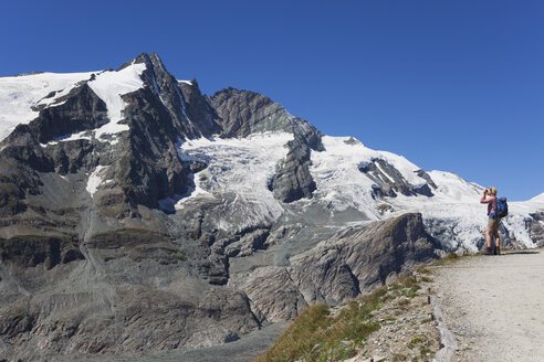 Austria, Carinthia, female hiker with binoculars watching Grossglockner peak, High Tauern National Park - GWF05534