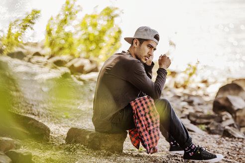 Young man wearing baseball cap sitting in nature - JATF01041
