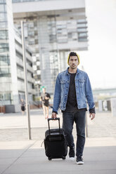 Germany, Cologne, portrait of young man pulling trolley - JATF01059