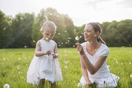 Mother and daughter with blowballs on meadow in summer - DIGF04592