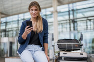 Smiling young businesswoman sitting outdoors with cell phone and suitcase - DIGF04608