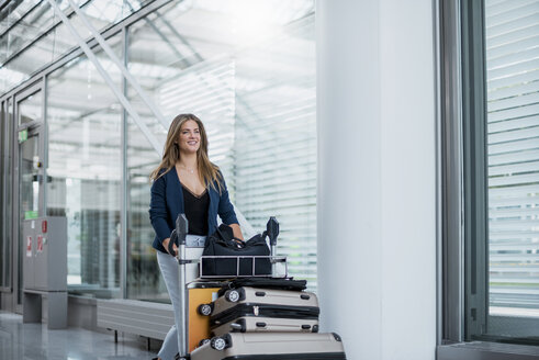 Smiling young woman pushing luggage trolley - DIGF04611