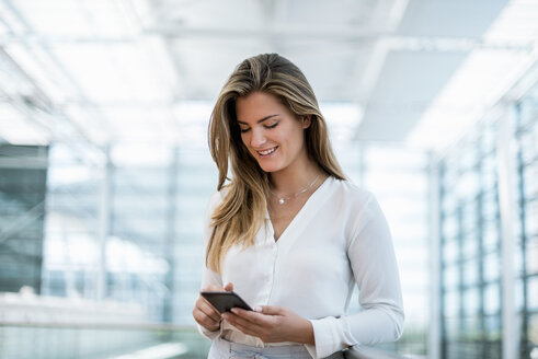 Smiling young woman standing at railing using cell phone - DIGF04617