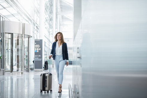 Young businesswoman walking with luggage at the airport - DIGF04623