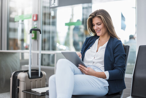 Young businesswoman with luggage sitting at waiting area using tablet - DIGF04626