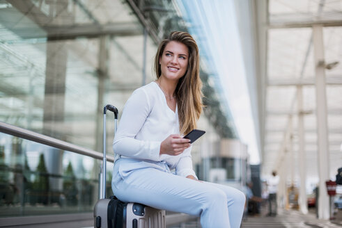 Smiling young businesswoman sitting on luggage with cell phone looking around - DIGF04632