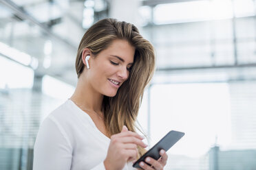 Smiling young woman wearing in-ear phone using cell phone - DIGF04641