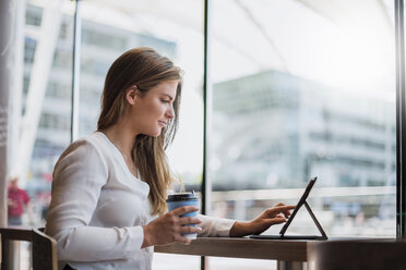 Young businesswoman in a cafe using tablet - DIGF04644