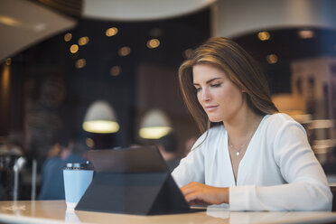Young businesswoman in a cafe using tablet - DIGF04650