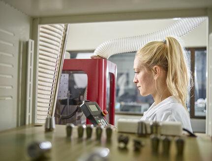 Female technician maintaining CNC machine - CVF00765