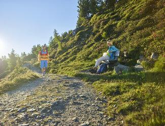 Austria, Tyrol, Couple hiking the Zirbenweg at the Patscherkofel, meeting at a bench - CVF00777