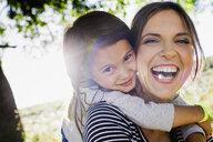 Portrait of mature woman giving daughter piggy back in sunlit park - CUF29089