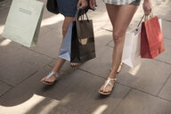 Bare legs and feet of two women carrying shopping bags on city street - CUF29131