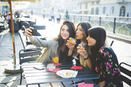Three young women posing for smartphone selfie at waterfront cafe - CUF29149