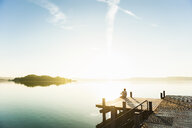 Young man sitting on corner of pier on sunlit lake, Woerthsee, Bavaria, Germany - CUF29242
