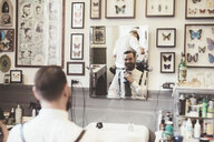 Mid adult man adjusting tie whilst looking in barber shop mirror - CUF29299
