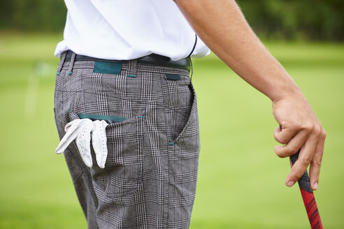 Cropped view of golfer holding golf club, golf glove in pocket - CUF29416