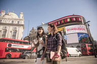 Two women backpackers with takeaway coffee, Piccadilly Circus, London, UK - CUF29434