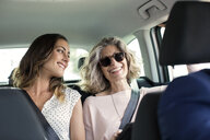 Two women chatting in back seat of car - CUF29452