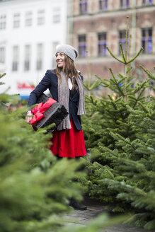 Mature woman with Christmas gift among Christmas trees - CUF29470