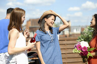 Female friends chatting and laughing at rooftop party - CUF29533