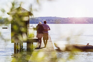 Rear view of young couple walking along pier on lake to boathouse, Schondorf, Ammersee, Bavaria, Germany - CUF29803