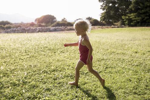 Female toddler running in field - CUF29827