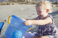 Happy female toddler playing on beach with toy bucket - CUF29842