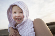 Portrait of female toddler between fathers legs on beach - CUF29848