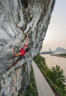 Male climber climbing Riverside crag in Yangshuo, Guangxi Zhuang, China - CUF29863