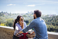 Young couple chatting on moped in Florence hills, Italy - CUF29878