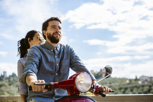 Young couple riding moped in Florence hills, Italy - CUF29881