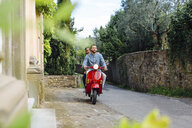 Young couple riding moped through village, Florence, Italy - CUF29884