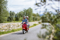 Young couple riding moped past olive grove, Florence, Italy - CUF29890