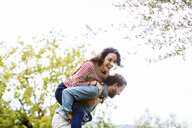 Young man giving girlfriend a piggy back in olive grove, Florence, Italy - CUF29893