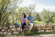 Portrait of young couple sitting on wall in olive grove, Florence, Italy - CUF29902