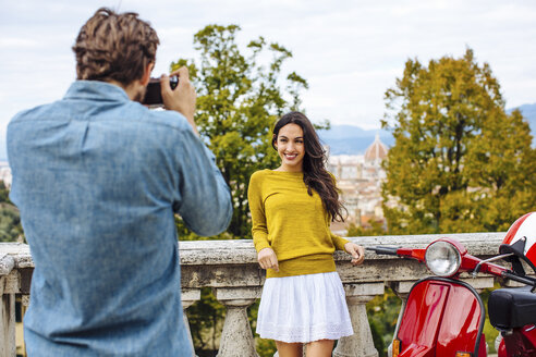 Young man photographing girlfriend in front of view from San Miniato church, Florence, Italy - CUF29908