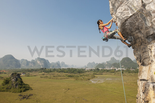 Female climber hanging from the Egg - a limestone cliff in Yangshuo, Guangxi Zhuang, China - CUF29953 - Henn Photography/Westend61