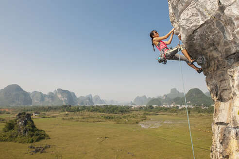 Female climber hanging from the Egg - a limestone cliff in Yangshuo, Guangxi Zhuang, China - CUF29953