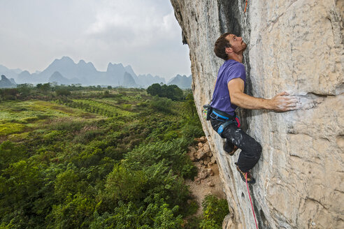 Elevated view of male climber climbing at white Mountain - a limestone cliff in Yangshuo, Guangxi Zhuang, China - CUF29959