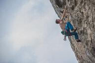 Young male climber climbing at white Mountain - a limestone cliff in Yangshuo, Guangxi Zhuang, China - CUF29962