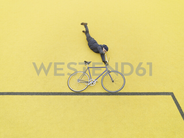 Urban cyclist doing illusionary stunt against yellow wall - CUF29980 - Soren Nielsen/Westend61