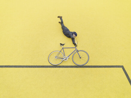 Urban cyclist doing illusionary stunt against yellow wall - CUF29980