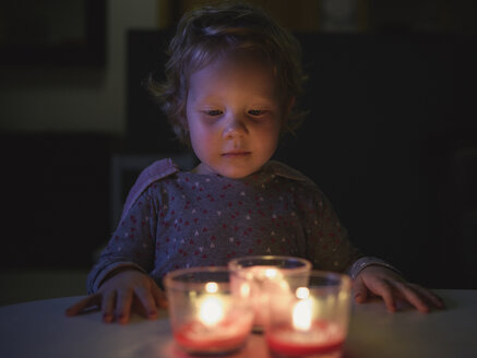 Preschool girl hands on table looking down at burning candles - CUF29992