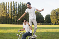 Two male friends fooling around on bicycle in park - CUF30031