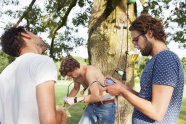 Male friends preparing decorative lights for park party - CUF30040