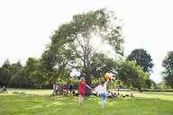 Rear view of two young women dancing with balloons at park party - CUF30046