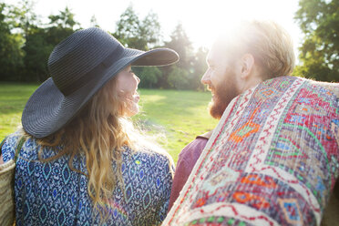 Rear view of romantic young couple carrying rug for picnic in park - CUF30058
