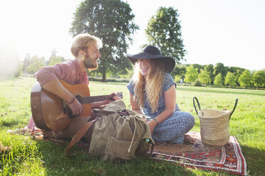 Romantic young couple playing acoustic guitar in park - CUF30061