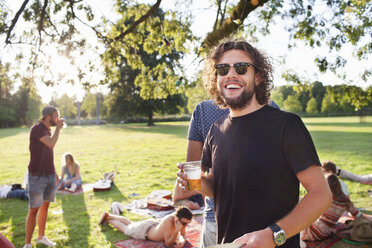 Portrait of young man drinking beer at group party picnic in park - CUF30067